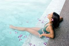 Free Girl Relaxing In Tropical Spa Pool With Flowers Royalty Free Stock Images - 140129269