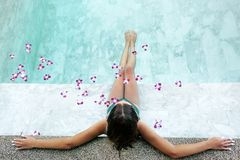 Free Girl Relaxing In Tropical Spa Pool With Flowers Royalty Free Stock Images - 140129449