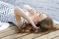 Girl relaxing on jetty near sea Stock Image