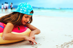 Girl relaxing with lilo on the beach Stock Photos