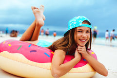 Girl relaxing with lilo on the beach Stock Photo