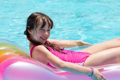 Girl relaxing on lilo in pool Stock Images