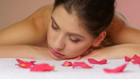 Girl relaxing after massage lying on towels with rose petals stock footage