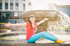 Girl relaxing near the fountain Stock Photography
