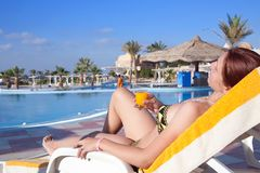 Girl relaxing with orange juice  at resort hotel Royalty Free Stock Photography