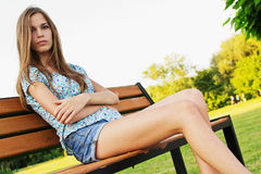 Girl relaxing on park bench Stock Photos