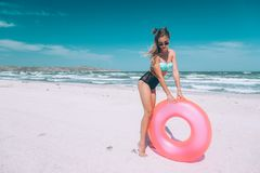 Girl relaxing on pink lilo on the beach royalty free stock photography