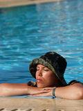Girl relaxing at the pool. Girl with a hat relaxing at the pool Stock Photography