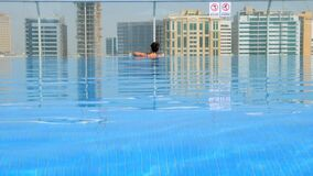 Girl relaxing in the pool on the roof with urban view on skyscraper.  stock video