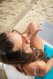 Girl Relaxing and reading on the beach Royalty Free Stock Images