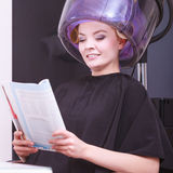 Girl relaxing reading magazine hairdryer by hairstylist in hair beauty salon Royalty Free Stock Photo