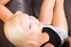 Girl relaxing on a Sofa Royalty Free Stock Photos