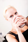 Girl relaxing on a Sofa drinking a cup of coffee Royalty Free Stock Images