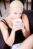 Girl relaxing on a Sofa drinking a cup of coffee Royalty Free Stock Photos