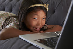 Girl Relaxing On Sofa At Home Using Laptop royalty free stock photos