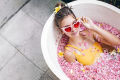 Girl relaxing in spa bath with flowers royalty free stock photos