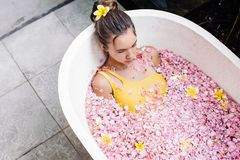 Girl relaxing in spa bath with flowers royalty free stock images