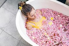 Girl relaxing in spa bath with flowers royalty free stock image