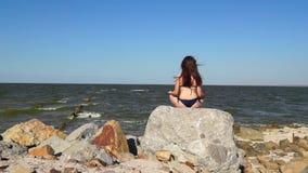 Girl relaxing on stone near sea stock video