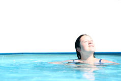 Girl relaxing in swimming pool. Girl in a swimming pool having a sunbath. Isolated on white, high key, shot suitable for holiday conceptual designs Royalty Free Stock Photo