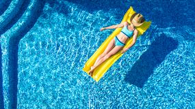 Girl relaxing in swimming pool, child swims on inflatable mattress and has fun in water on family vacation, tropical holiday. Resort, aerial drone view from royalty free stock images