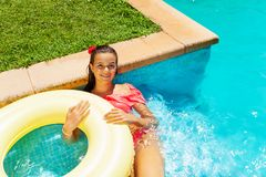 Girl relaxing in swimming pool with swim ring royalty free stock photos