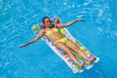 A girl is relaxing in a swimming pool Stock Photography