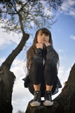 Girl Relaxing on a Tree. Thoughtful young girl relaxing on a tree on a sunny evening Stock Photos