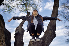 Girl Relaxing on a Tree. Young girl enjoying her freedom on a tree on a sunny evening Royalty Free Stock Images