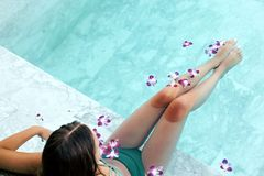 Girl relaxing in tropical spa pool with flowers royalty free stock photos