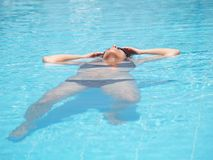 Girl relaxing in the water. Floating girl relaxing in the pool Royalty Free Stock Image