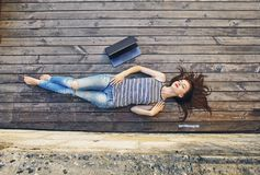 Girl relaxing on a wooden floor . Relax, rest, education concept, recreation . Stock Photography
