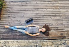 Girl relaxing on a wooden floor . Relax, rest, education concept, recreation . Young attractive girl relaxing on a wooden floor . Relax, rest, education concept Royalty Free Stock Photography