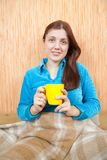 Girl relaxing with a yellow cup at home Stock Photography