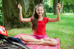 Girl relaxing in yoga pose  in a park. Girl relaxing in yoga pose on grass in a park Royalty Free Stock Photo