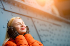 Girl relishing music on headphones Stock Image