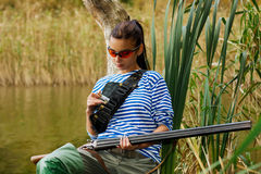 Girl reloads the gun on nature in a swamp. Royalty Free Stock Image