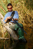 Girl reloads the gun on nature in a swamp. Royalty Free Stock Photography