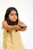 Girl with remote. 8 year old girl changing tv channel with remote control royalty free stock image
