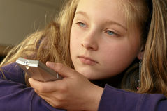 Girl with remote control. Portrait of young girl with television remote control indoors Stock Image