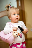 Girl with remote control. Cute young blond haired girl with teddy bear in bag and remote control device Stock Photos