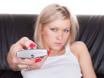 Girl with remote control. On the sofa Stock Image