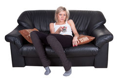 Girl with remote control. On the sofa Stock Photos