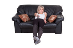 Girl with remote control. On the sofa Royalty Free Stock Photos