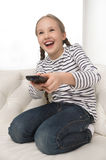 Girl with remote control. Stock Photos