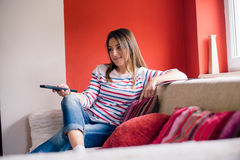 Girl with remote control on sofa. In living room Royalty Free Stock Photos