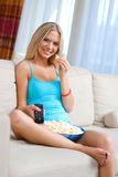 Girl with remote and popcorn Royalty Free Stock Photos
