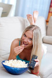 Girl with remote and popcorn Royalty Free Stock Photography