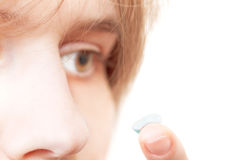 Girl removes contact lens from eye Royalty Free Stock Images