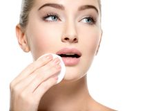 Girl removes makeup cotton ball from face Stock Photography
